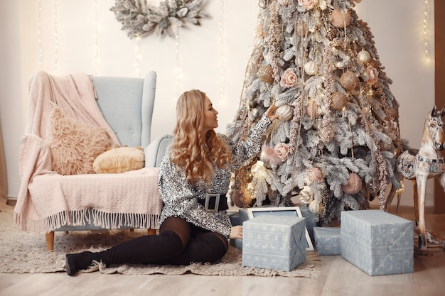 クリスマスツリーの近くのエレガントな女性