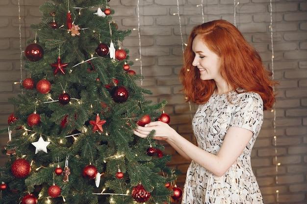 クリスマスの木の近くのエレガントな女性。シャンパンで家にいる女性。