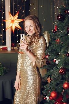 크리스마스 트리 근처 우아한 아가씨입니다. 샴페인 집에서 여자입니다.