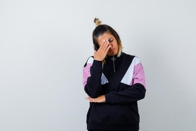 Elegant lady rubbing forehead, keeping eye shut in sweatshirt and looking exhausted