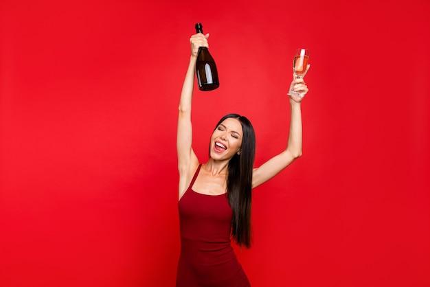 Элегантная дама с коктейлем в руке поет поднятыми руками, закрывает глаза