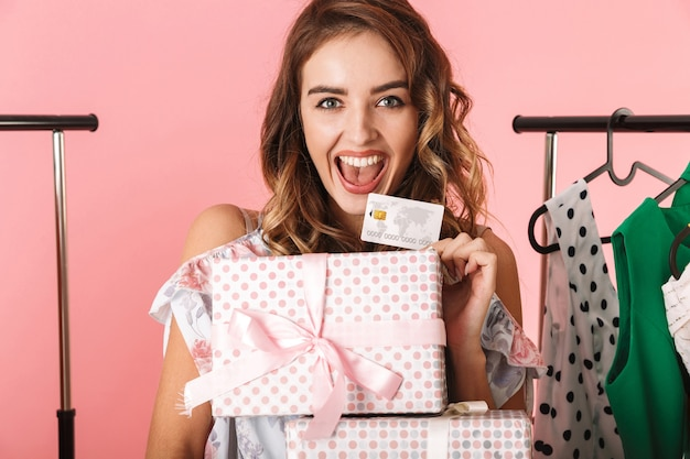 Elegant lady with purchase standing in store near clothes rack and holding credit card isolated on pink