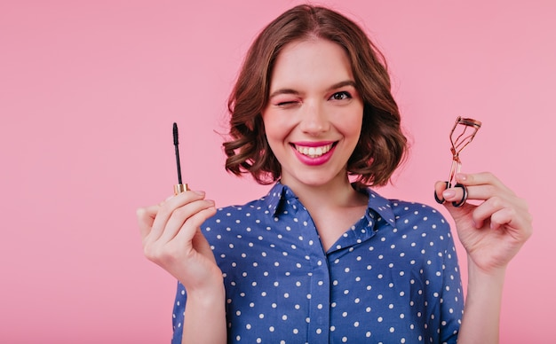 Elegant lady with short hairstyle doing her eye lashes and laughing. indoor photo of smiling curly woman holding mascara on pink wall.