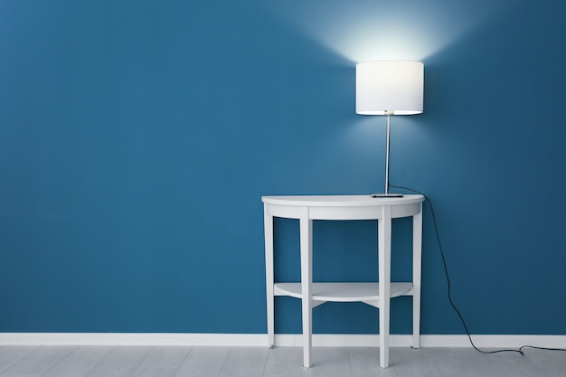컬러 벽 근처 테이블에 우아한 램프