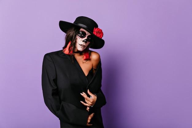 Elegante modello femminile latino in posa per il servizio fotografico di halloween. incredibile giovane donna con la pittura del viso spettrale in piedi sul muro viola.