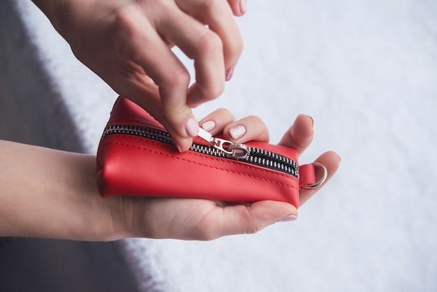 우아한 가죽, 빨간색 키 암밴드. 가죽 포켓 키 액세서리 시연. 자물쇠에 가죽 작은 핸드백