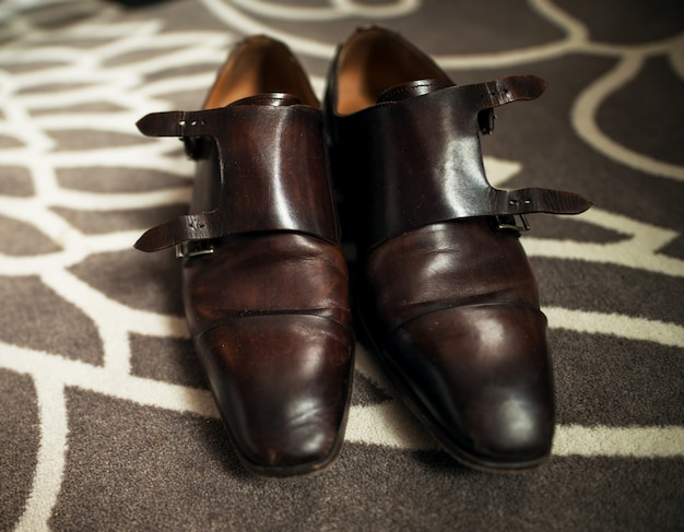 Elegant leather shoes on abstract carpet
