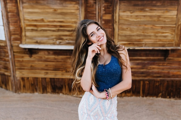 Elegant long-haired girl in cute bracelets playfully smiling, while posing in front of timbered building