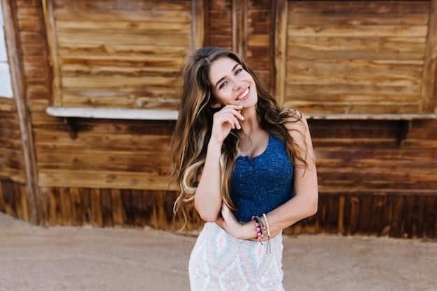 Элегантная длинноволосая девушка в милых браслетах игриво улыбается, позируя перед бревенчатым домом