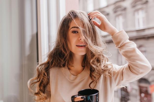 朝にポーズをとって、窓の横でコーヒーを飲むエレガントな長髪の女性