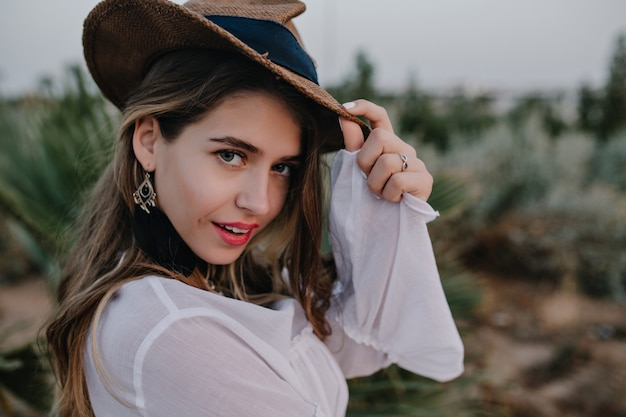 Elegant long-haired woman in stylish hat looks, while walking in beautiful exotic park. close-up portrait of pretty young woman in trendy earrings and shirt posing with enigmatic face expression