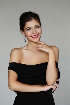 エレガントな素敵な女性が黒のドレスでポーズ 無料写真