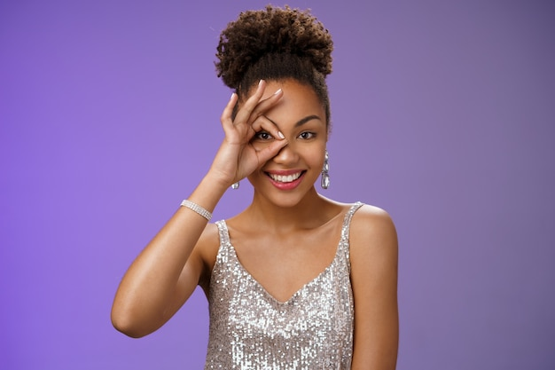 Elegant lucky confident feminine african-american woman in silver fashionable dress show okay ok gesture on eye peeking forward gladly smiling self-assured like perfection, stand blue background.