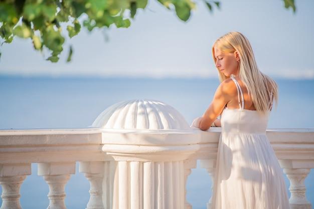 海辺の遊歩道で夕日の景色を楽しむ白いドレスを着たエレガントで豪華な女性