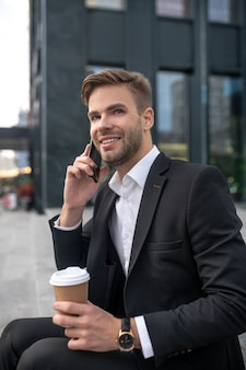 Elegant male businessman having coffee and talking on the phone