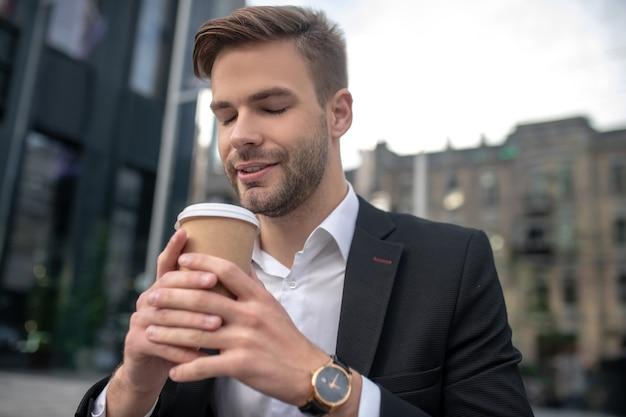 Элегантный мужчина-бизнесмен пахнет кофе и выглядит расслабленным