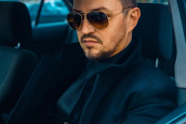 선글라스로 차를 운전하는 검은 양복을 입은 우아한 남성