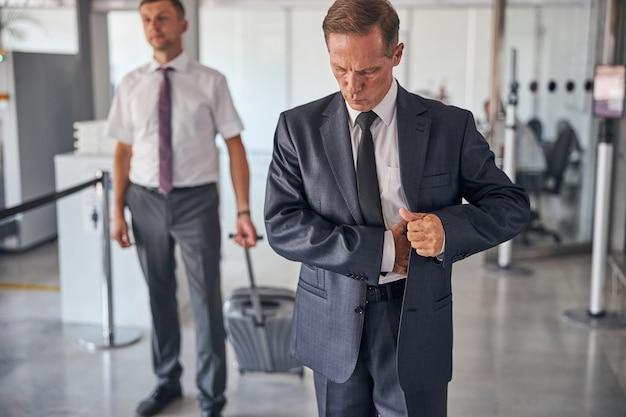 넥타이와 양복을 입은 우아한 남성이 조수가 여행 가방을 들고 있는 동안 공항에서 걷고 있다