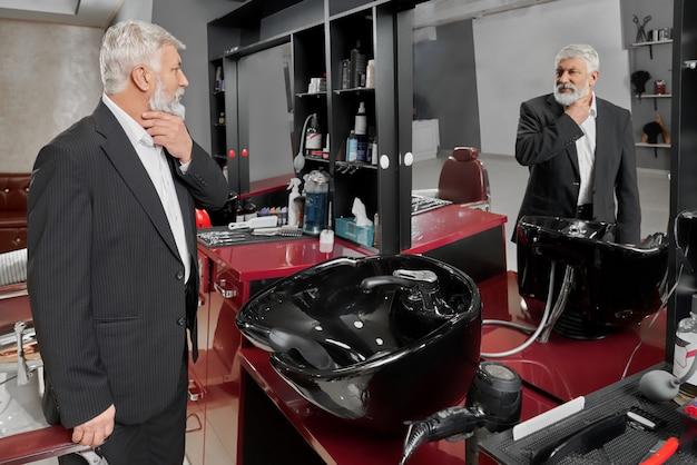 Элегантный мужчина стоит в парикмахерской перед укладкой бороды