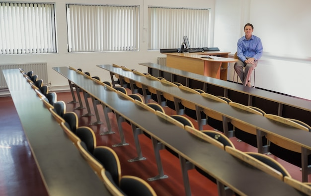 Elegant male teacher sitting in the lecture hall