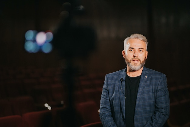 Elegant male theatre and movie director giving an interview in the auditorium
