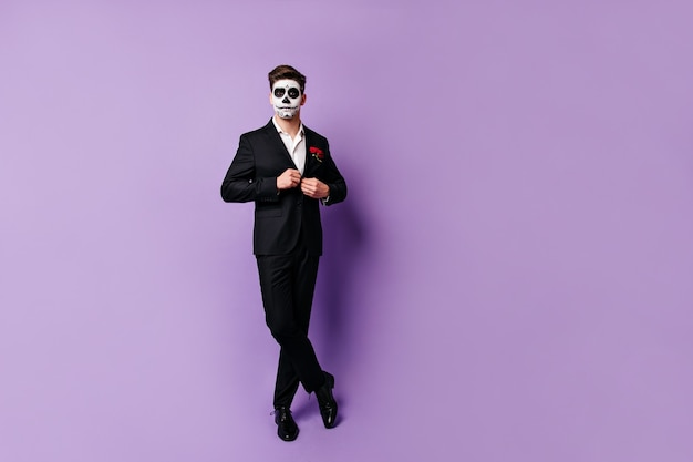Элегантный мужчина застегивает черный классический пиджак и позирует в непринужденной студии в маске для маскарада.