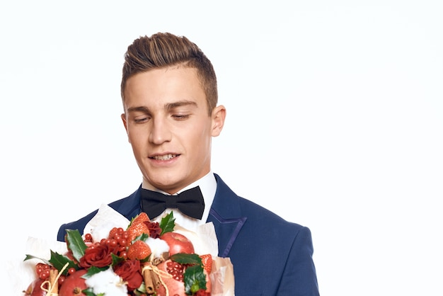 An elegant man in a classic suit with a bow tie holds a bouquet of flowers in his hand