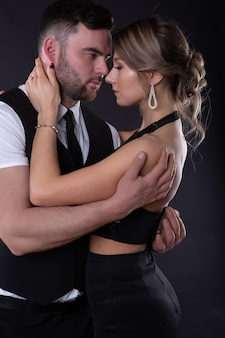 Elegant man embraces his sexy woman who closed her eyes with pleasure