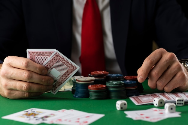 Elegant man at green playing table with gambling chips and cards playing poker and blackjack in casino.