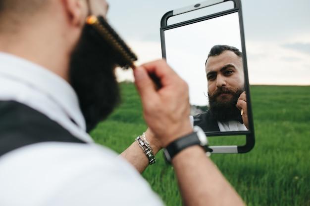 Элегантный мужчина держит зеркало и расчесывает бороду