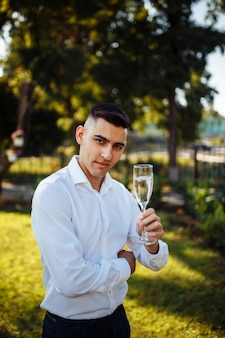 Elegant man holding glasses of champagne at luxury wedding. a man with a glass of champagne.