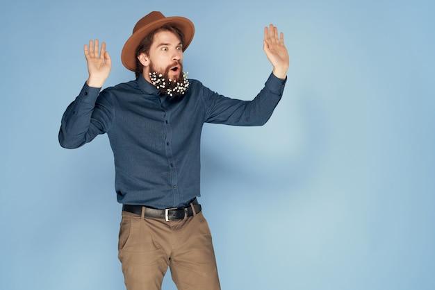 Элегантный мужчина в шляпе с цветами в бороде, уход за волосами в современном стиле