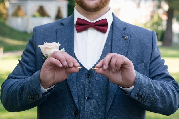 Элегантный мужчина в костюме-тройке с бордовым галстуком-бабочкой держит два обручальных кольца перед свадебной церемонией