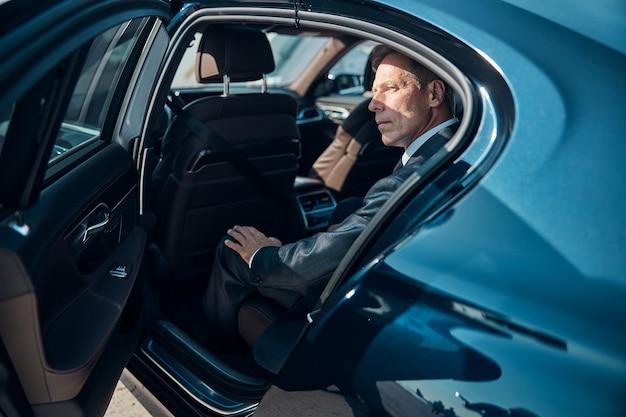 Элегантный мужчина в классическом костюме едет в автомобиле с водителем после прибытия в аэропорт