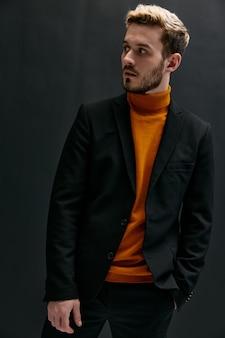 クラシックなスーツのエレガントな男性オレンジ色のセーターコート黒の背景の季節のトレンド。高品質の写真