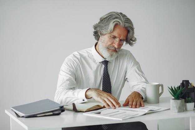 オフィスでエレガントな男。白いシャツのビジネスマン。男はドキュメントを扱います。