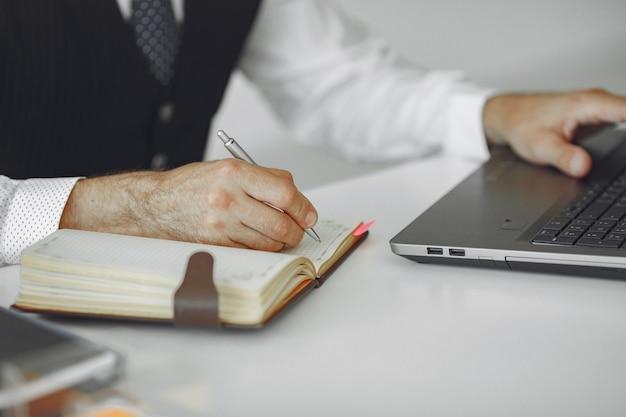 Элегантный мужчина в офисе. бизнесмен в белой рубашке. человек работает с ноутбуком.