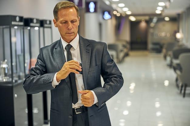 Элегантный мужчина в костюме и галстуке покидает гостиную перед вылетом и кладет сотовый телефон в карман