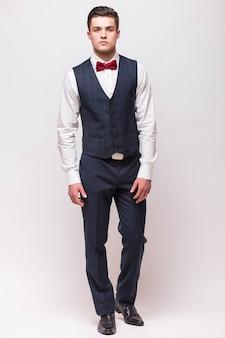 白い壁に分離されたスーツのエレガントな男