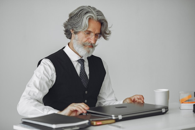 Elegant man in office. businessman in white shirt. man works with laptop.