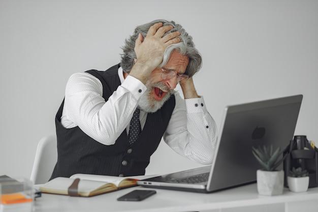 Uomo elegante in ufficio. uomo d'affari in camicia bianca. l'uomo lavora con il laptop.