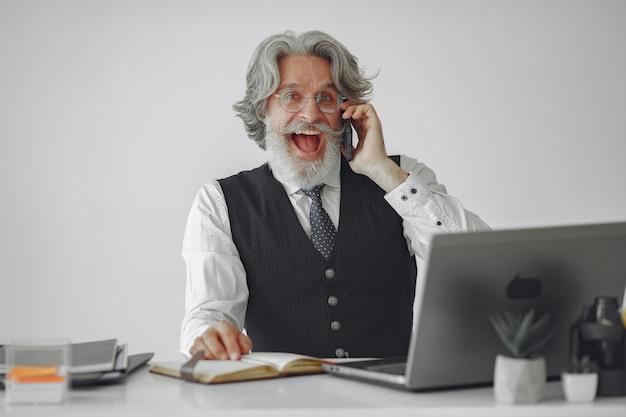 Uomo elegante in ufficio. uomo d'affari in camicia bianca. l'uomo lavora con il telefono.