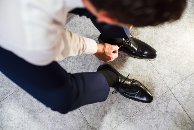 An elegant man puts on black, leather, formal shoes.