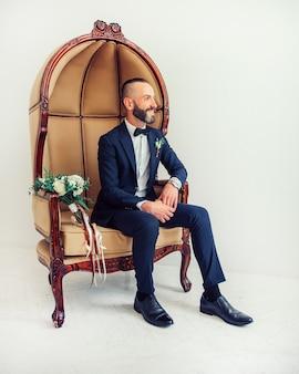 우아한 남자가 의자에 앉아 어딘가에 찾고 있습니다.