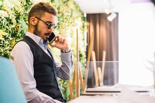 Elegant man speaking on smartphone in cafe