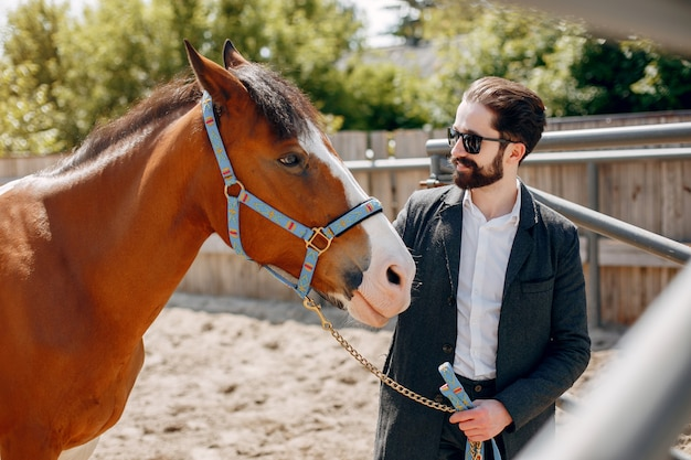 Elegant man standing next to horse in a ranch