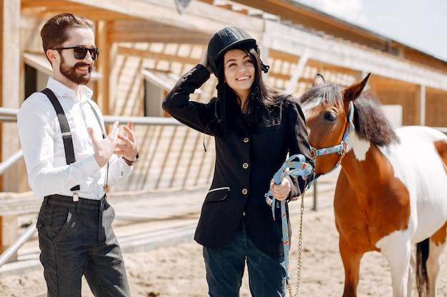 Элегантный мужчина стоит рядом с лошадью на ранчо с девушкой