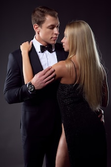 An elegant man in a suit with a bow tie gently embraces a sexy woman.