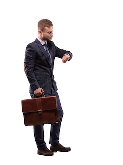 The elegant man in a suit with a briefcase looking at his watch
