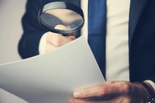 Elegant man using magnifier on documents